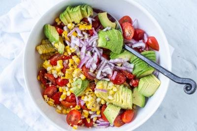 Corn Tomato Avocado Salad in a bowl with dressing