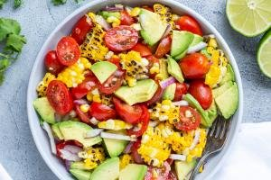 Corn Tomato Avocado Salad in a bowl and limes