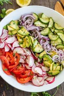 Salad in a bowl, tomatoes, radishes, avocado, onion and cucumber with dressing on top