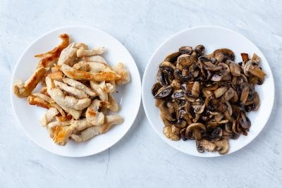 Two plates, one with mushrooms and one with chicken
