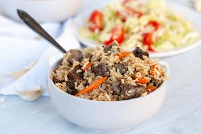 Plov or pilaf in a bowl with salad in background