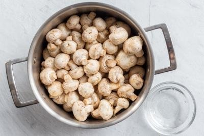 Mushrooms in a pot with vinegar next to it