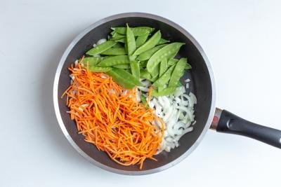 Carrots, onions and peas in a skillet