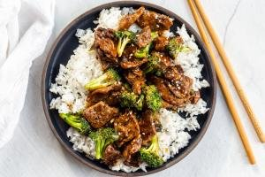 Beef and broccoli over rice in a plate