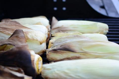 Corn with peel on a grill