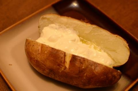 Baked potato with sour cream in it