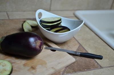 Full eggplant on a cutting board with horizontally cut circle slices in a bowl next to it