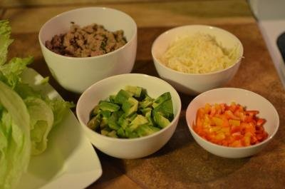 All ingredients for turkey lettuce wraps in separate bowls; avocados, ground turkey, cheese, and peppers