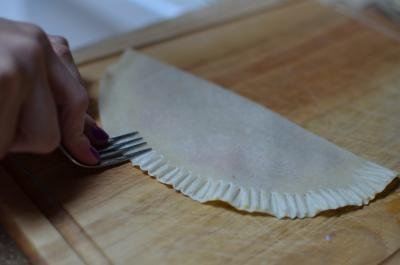 Tortilla being pinched together using a fork to press both sides together