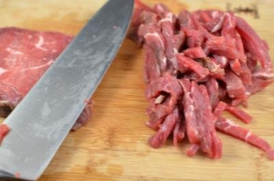 Beef being sliced into thin slices on a cutting board