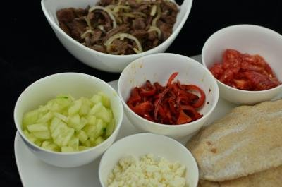 Bowls with ingredients for the pita pockets in each bowl; cucumbers, feta cheese, tomatoes, peppers and beef