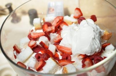 In large glass bowl layer angel cake, fruits and cream over top