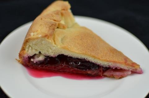 A slice of plum pie on a plate