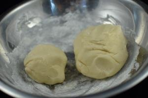 Pie dough split into 2 balls, 1 slightly bigger then the other, placed into the same bowl
