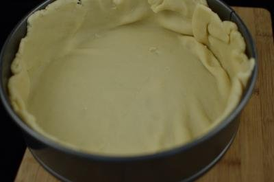 Dough placed around and on the sides of the baking pie tin