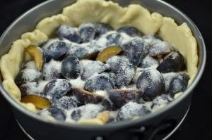 Plums sliced in halves and placed skin side up into the inside of the dough covered pie tin, sugar is sprinkled on the top of the plums