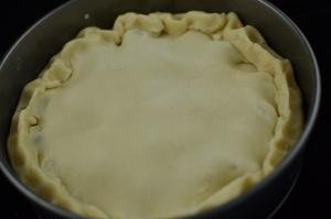 The top of the pie covered with dough and connected together with the sides of the pie