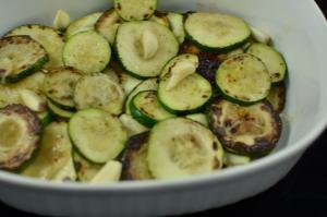 Sliced and fried zucchini pieces with garlic pieces in a bowl