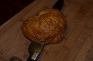 A croissant being sliced in half horizontally
