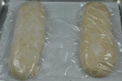 2 loaves of Oatmeal Wheat Bread on a baking sheet covered in plastic wrap