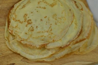 A stack of cooked crepes on a cutting board