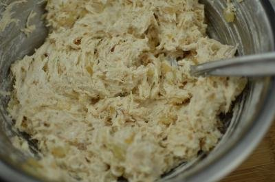 A mixture of shred chicken mixed with cream cheese and onions in a bowl