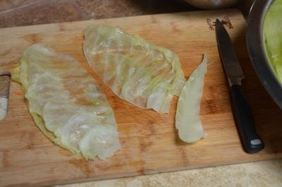 A cabbage leaf cut in half and the hard center being cut out