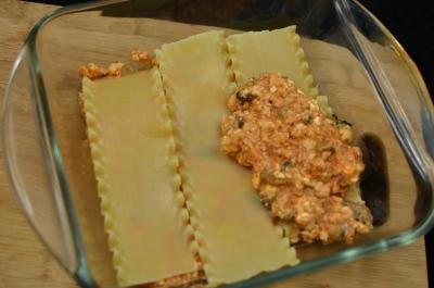 Lasagna noodles in a baking sheet with sauce