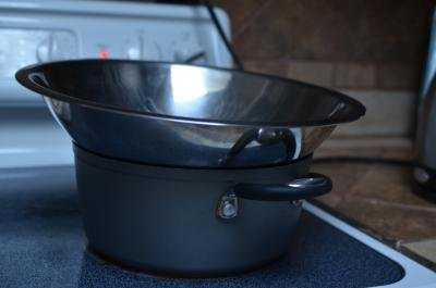 Pot with bowl on top on a stove top