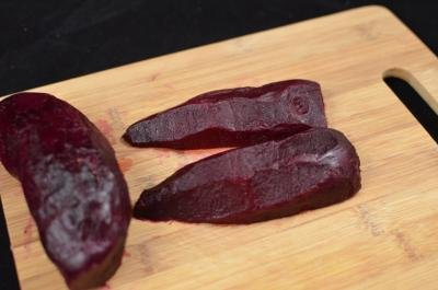 A beet on a cutting board being sliced into long vertical slices