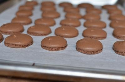 Cooked chocolate macarons on a baking sheet lined with parchment paper