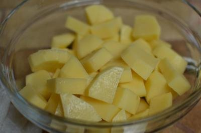 Peeled potatoes diced into small cubes in a bowl