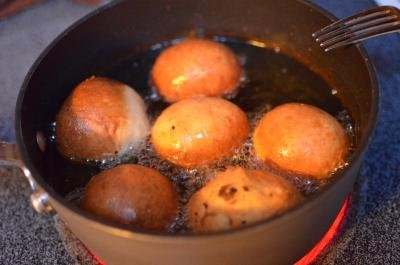 Russian Sweet Piroshky frying in oil in a pot