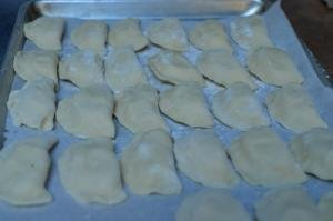 Pierogi on a baking sheet covered in parchment paper and floured