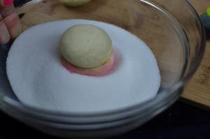 Peach Cookie being dipped into sugar