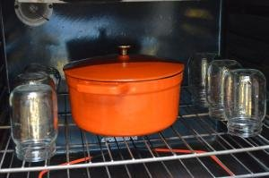 An oven filled with jars that are inside down and a ceramic pot with the stewed meat