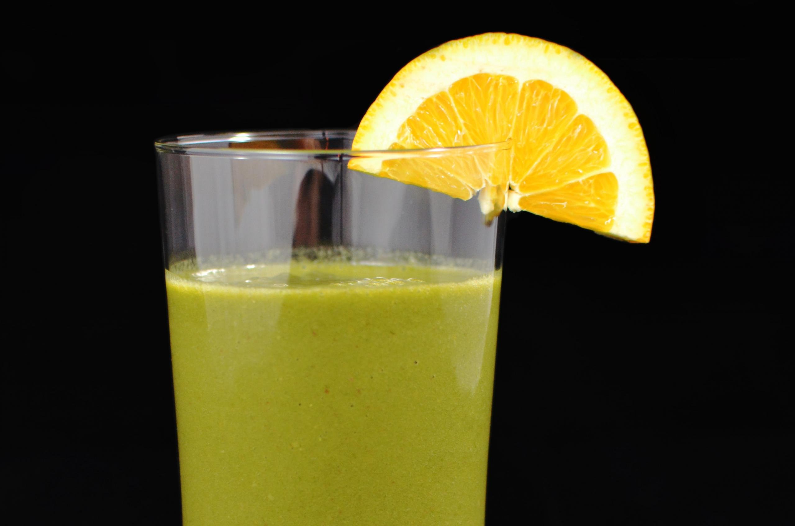 Green Smoothie with a orange slice on the brim of the glass