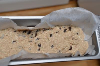 Dough in a baking pan that is lined with parchment paper