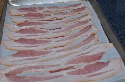 Bacon layer out on a baking sheet that is lined in parchment paper