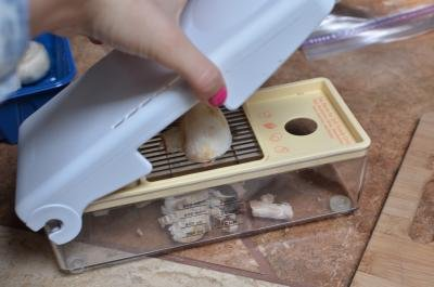 Mushroom halves being sliced using a plastic mushroom slicer