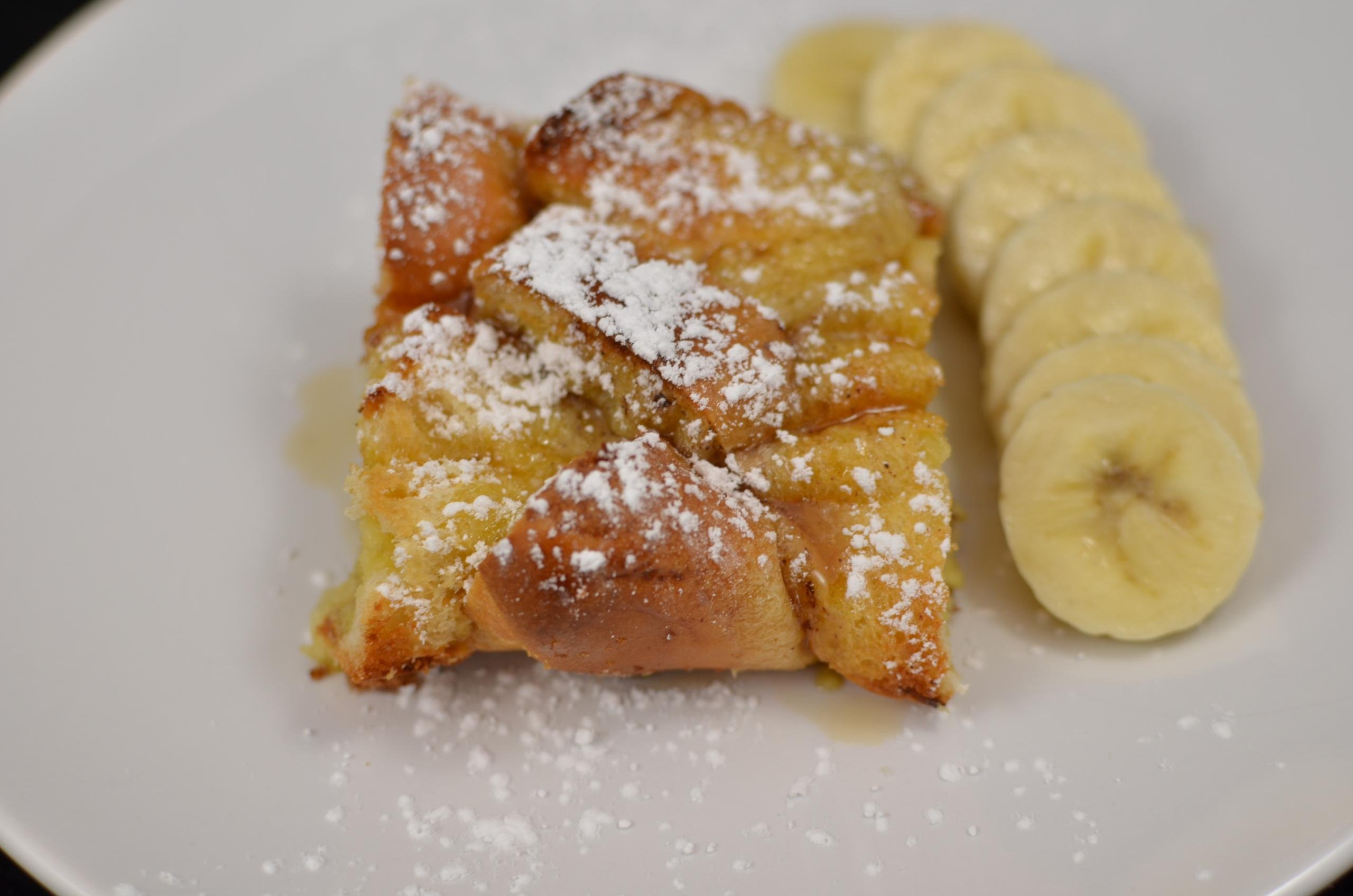 Baked French Toast on a plate with powdered sugar sprinkled on top and a row of banana slices