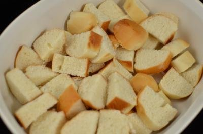 White bread sliced into 1inch squares placed on a ceramic baking pan