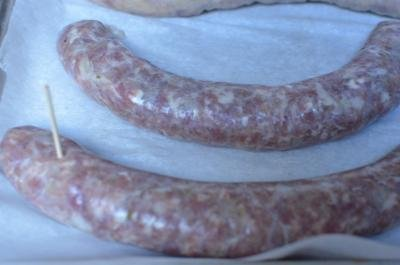 Sausages are placed on a baking sheet and a toothpick is used to make small holes in the sausage casing