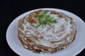 Layers of the liver cake being stacked on top of each other; liver crepe then mayo, garlic and dill spread and repeated