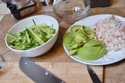 Ingredients for California sushi bowl; thin sliced cucumber in a bowl and avocado and crab meat on a plate