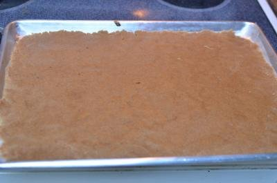 Coconut bar mixture being spread on a baking sheet