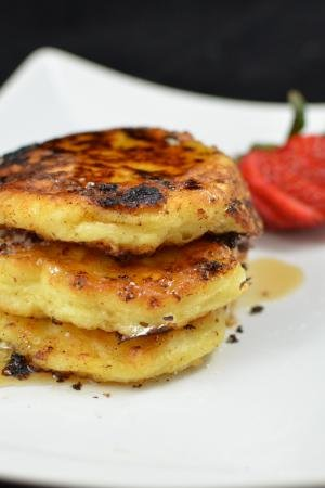 3 cottage cheese pancakes stacked onto top of each other on a plate