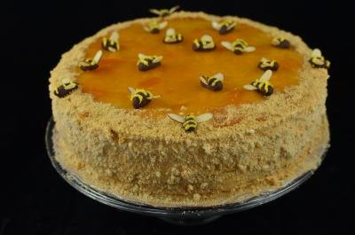 Full honey cake on a plate decorated with chocolate bees