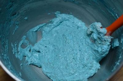 Blue colored whipped egg whites and sugar being stirred together with flout and sugar dry mixture
