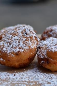 Farmer's Cheese Doughnuts sprinkled with powered sugar on top of a cutting board